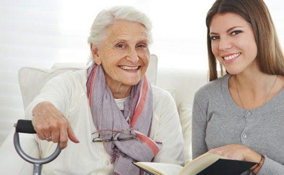 Femme avec un livre à la main s'occupant d'une personne agée